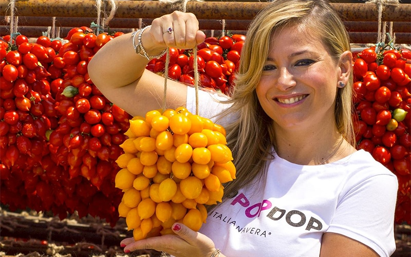 Italianavera producer holding her tomatoes