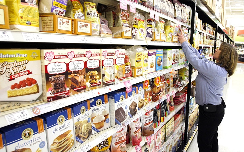 A woman choosing between different gluten free products in the supermarket aisle