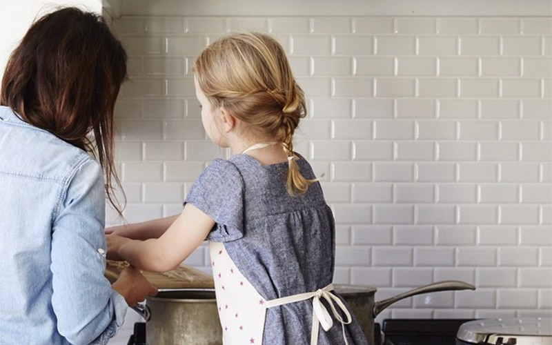 A Mom and her little daughter cooking together