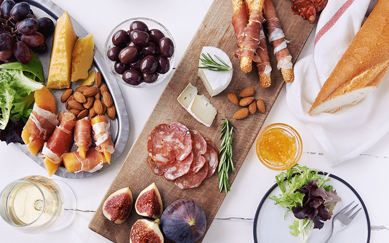 A platter of fruit, cheese and cured meats with Prosecco