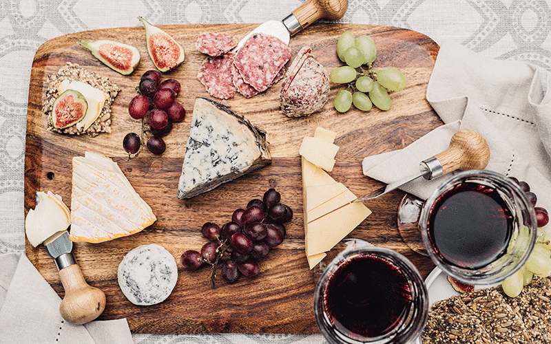 A platter of cured meats and cheese with red wine